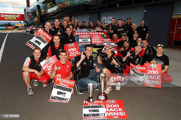 Garth Tander and Nick Percat drivers of the Toll Holden Racing Team Holden pose with the Peter Brook Trophy and pit crew after winning the Bathurst...