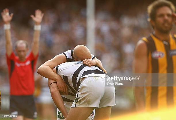 Gary Ablett and Brad Ottens of the Cats celebrate victory as Chance Bateman of the Hawks looks dejected as the siren sounds during the round two AFL...