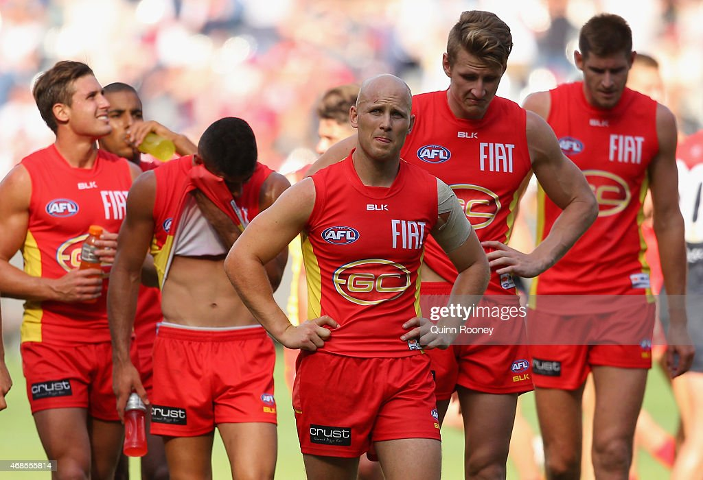 Gary Ablett and his Suns team mates look dejected as they leave the field after losing the round one AFL match between the Melbourne Demons and the Gold Coast Suns at Melbourne Cricket Ground on April 4, 2015 in Melbourne, Australia.