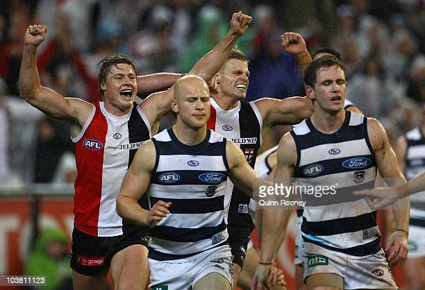 Gary Ablett and Joel Selwood of the Cats look dejected as Clinton Jones and Nick Riewoldt of the Saints celebrate around them after winning the AFL...