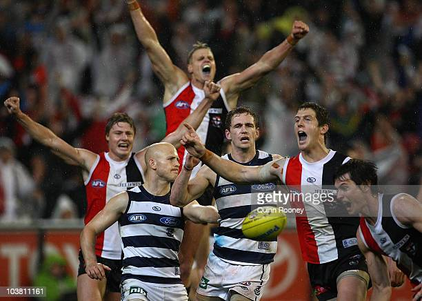 Gary Ablett and Joel Selwood of the Cats look dejected as Clinton Jones, Nick Riewoldt and Nick Dal Santo of the Saints celebrate around them after...