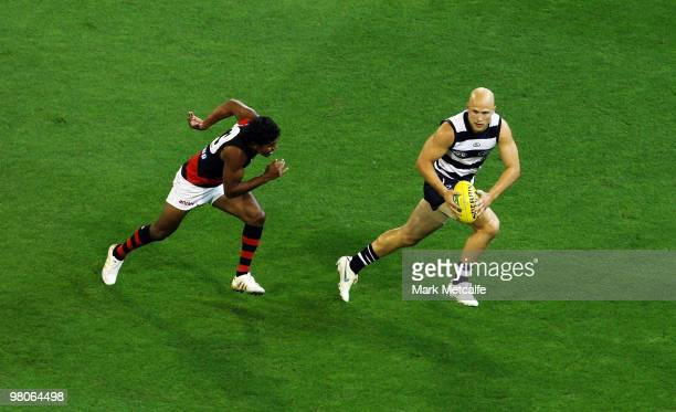 Gary Ablett of the Cats evades the tackle of Alwin Davey of the Bombers during the round one AFL match between the Geelong Cats and the Essendon...