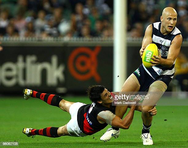 Gary Ablett of the Cats is tackled by Angus Monfries of the Bombers during the round one AFL match between the Geelong Cats and the Essendon Bombers...