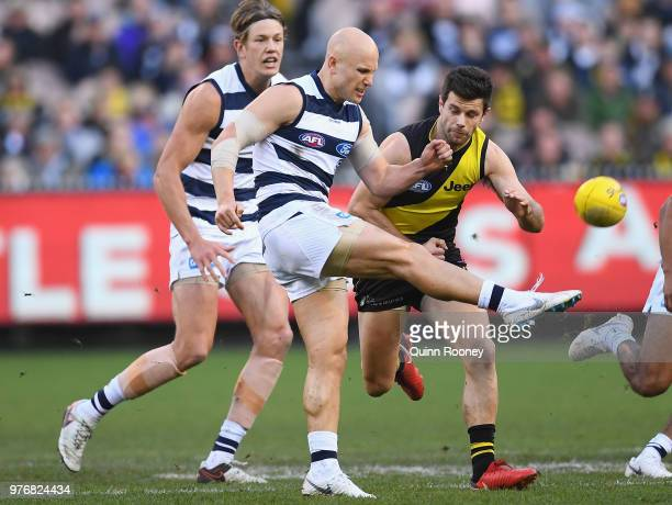 Gary Ablett of the Cats kicks whilst being tackled by Trent Cotchin of the Tigers during the round 13 AFL match between the Geelong Cats and the...
