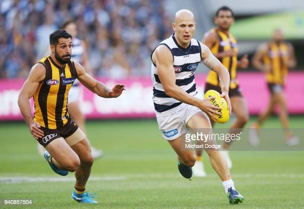 Gary Ablett of the Cats runs with the ball from Paul Puopolo of the Hawks during the round two AFL match between the Geelong Cats and the Hawthorn...