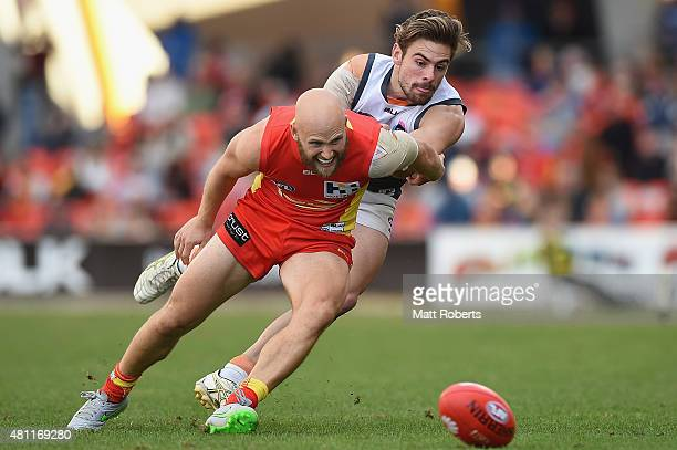 Gary Ablett of the Suns competes for the ball against Stephen Coniglio of the Giants during the round 16 AFL match between the Gold Coast Suns and...