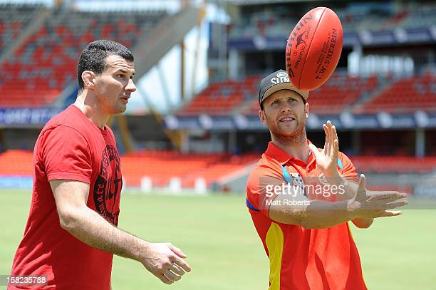 Gary Ablett of the Suns explains how to handball an AFL football to Anthony Perosh during a UFC media session with the AFL Gold Coast Suns at...