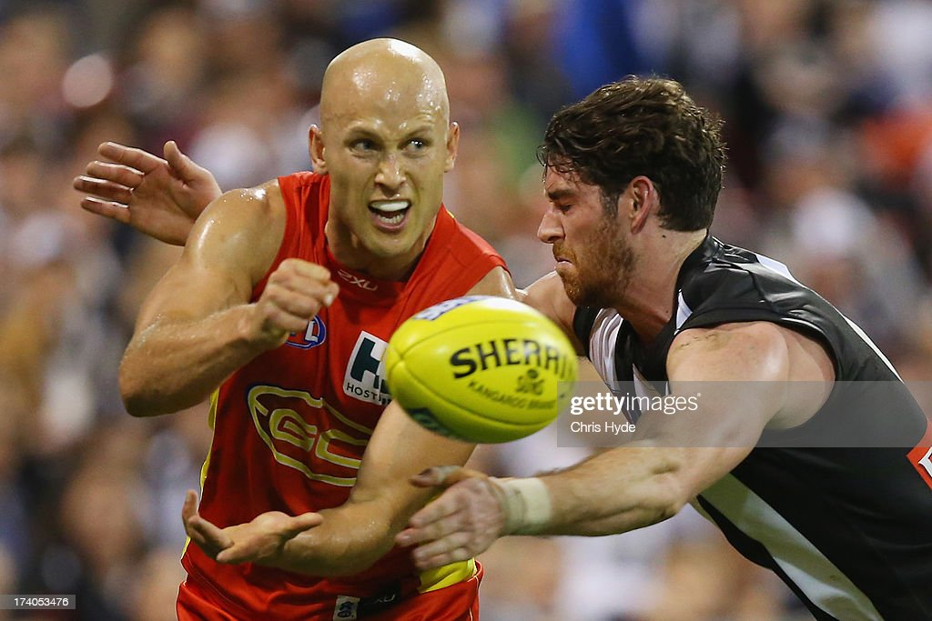 Gary Ablett of the Suns handballs while tackled by Tyson Goldsack of the Magpies during the round 17 AFL match between the Gold Coast Suns and the Collingwood Magpies at Metricon Stadium on July 20, 2013 in Gold Coast, Australia.