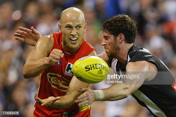 Gary Ablett of the Suns handballs while tackled by Tyson Goldsack of the Magpies during the round 17 AFL match between the Gold Coast Suns and the...