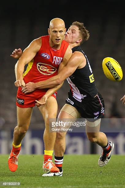 Gary Ablett of the Suns handballs whilst being tackled by Jack Billings of the Saints during the round nine AFL match between the St Kilda Saints and...