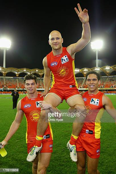 Gary Ablett of the Suns is chaired from the field by team mates Jaeger O'Meara and Harley Bennell after playing his 250th game during the round 20...