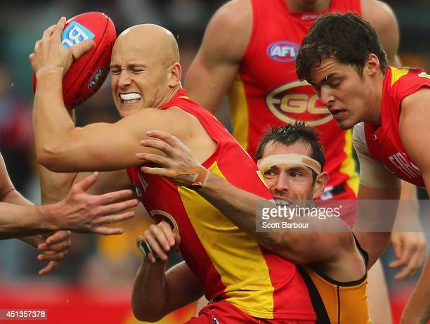 Gary Ablett of the Suns is tackled by Luke Hodge of the Hawks during the round 15 AFL match between the Hawthorn Hawks and the Gold Coast Suns at...
