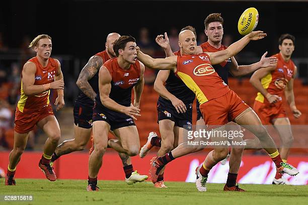 Gary Ablett of the Suns is tackled during the round seven AFL match between the Gold Coast Suns and the Melbourne Demons at Metricon Stadium on May 7...