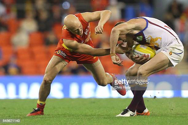 Gary Ablett of the Suns reacts after injuring his hand in a tackle against Mitch Robinson of the Lions during the round 16 AFL match between the Gold...