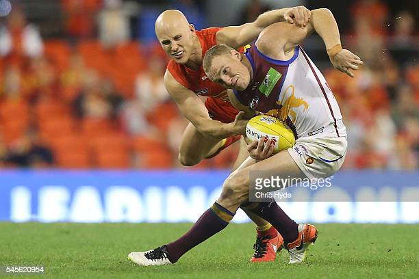 Gary Ablett of the Suns tackle Mitch Robinson of the Lions and injures his hand during the round 16 AFL match between the Gold Coast Suns and the...