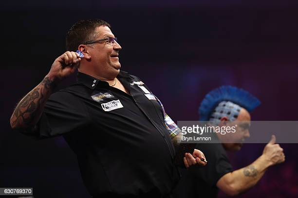 Gary Anderson of Great Britain throws his flights into the crowd after beating Peter Wright of Great Britain in their semifinal match on day fourteen...