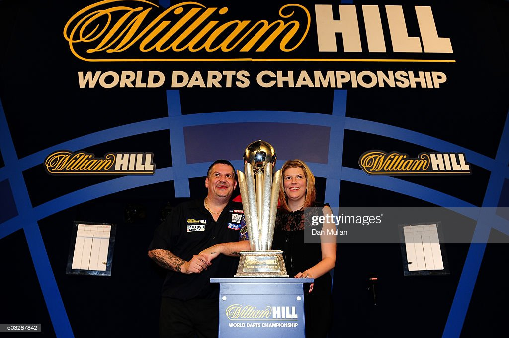 Gary Anderson of Scotland (L) celebrates with his partner Rachel Ford and the Sid Waddell Trophy after defeating Adrian Lewis of England in the final match during Day Fifteen of the 2016 William Hill PDC World Darts Championships at Alexandra Palace on January 3, 2016 in London, England.