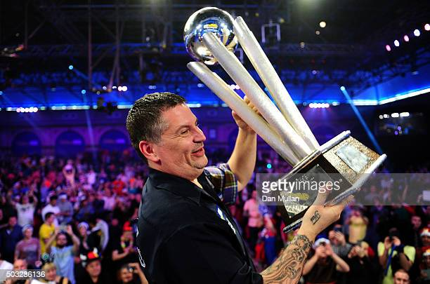 Gary Anderson of Scotland celebrates with the Sid Waddell Trophy after defeating Adrian Lewis of England in the final match during Day Fifteen of the...