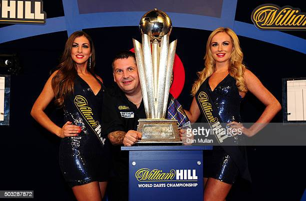 Gary Anderson of Scotland celebrates with the Sid Waddell Trophy alongside the oche girls after defeating Adrian Lewis of England in the final match...