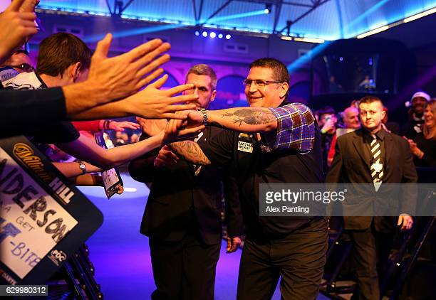 Gary Anderson of Scotland greats supporters during the walk on prior to his first round match against Mark Frost of England during day one of the...