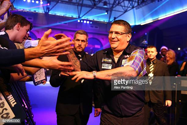 Gary Anderson of Scotland greets supporters during the walk on prior to his first round match against Mark Frost of England during day one of the...