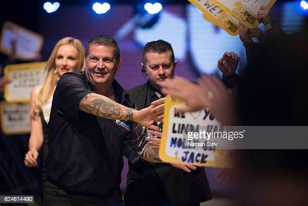 Gary Anderson of Scotland is greeted by the crowd ahead of his match against James Wade of England during the SINGHA Beer Grand Slam of Darts at...