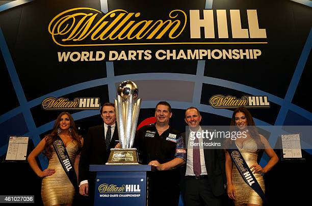 Gary Anderson of Scotland poses with AP McCoy innovation director of William Hill Jamie Hart and the William Hill walk on girls after defeating Phil...