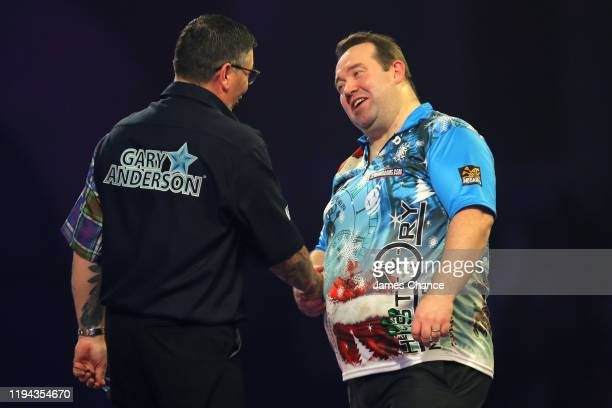 Gary Anderson of Scotland shakes hands with Brendan Dolan of Northern Ireland after the Second Round match between Gary Anderson and Brendan Dolan on...