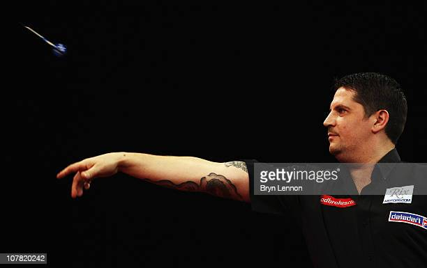 Gary Anderson of Scotland throws against Andy Smith of England during day 12 in the 2011 Ladbrokescom World Darts Championship at Alexandra Palace on...