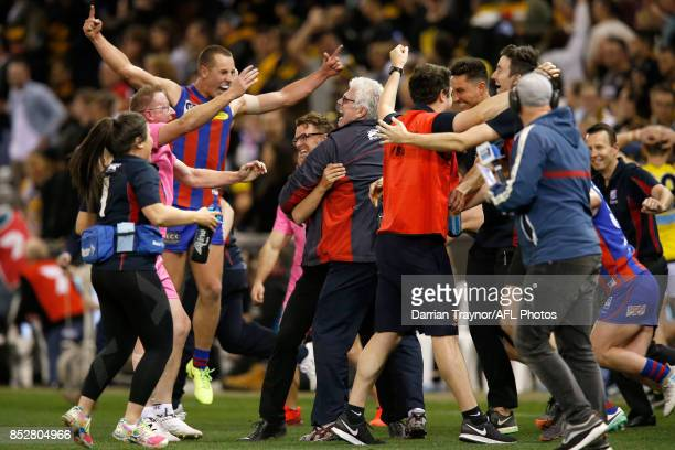 Gary Ayres senior coach of Port Melbourne is embraced by other coaching staff as the final siren sounds during the VFL Grand Final match between...