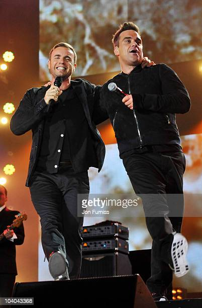 Gary Barlow and Robbie Williams on stage at the Heroes Concert at Twickenham Stadium on September 12 2010 in London England
