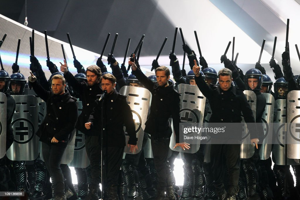 Gary Barlow, Jason Orange, Mark Owen, Howard Donald and Robbie Williams of Take That perform onstage at The Brit Awards 2011 held at The O2 Arena on February 15, 2011 in London, England.