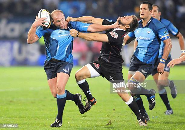 Gary Botha of the Blues is tackled by Rory Kockott of the Sharks during the Super 14 Round 12 match between the Vodacom Blue Bulls and the Sharks at...