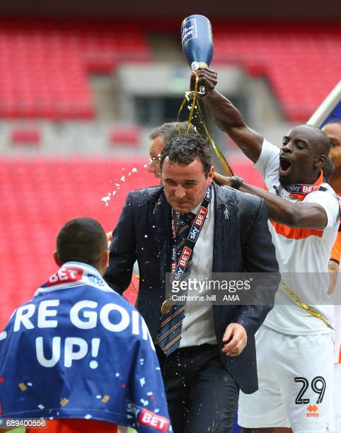 Gary Bowyer the head coach / manager of Blackpool is covered by champagne by his players as they celebrate promotion during the Sky Bet League Two...