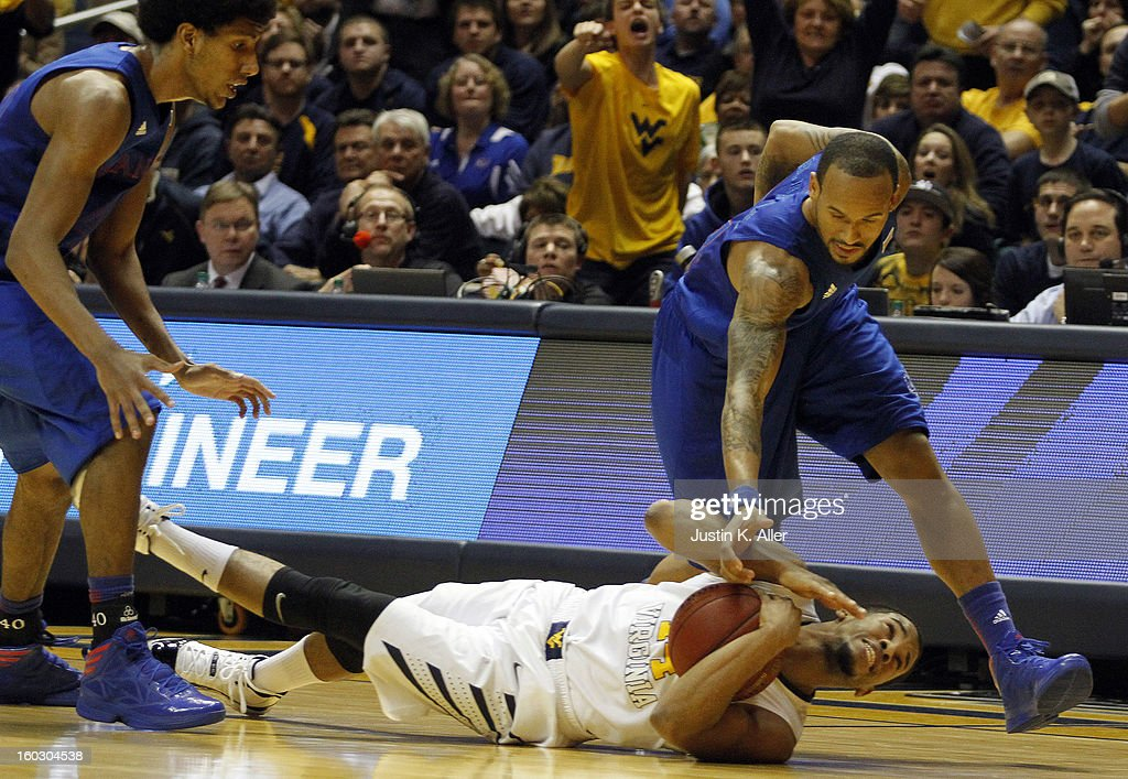 Gary Browne #14 of the West Virginia Mountaineers and Ben McLemore #23 of the Kansas Jayhawks battle for a loose ball at the WVU Coliseum on January 28, 2013 in Morgantown, West Virginia. The Jayhawks defeated WVU