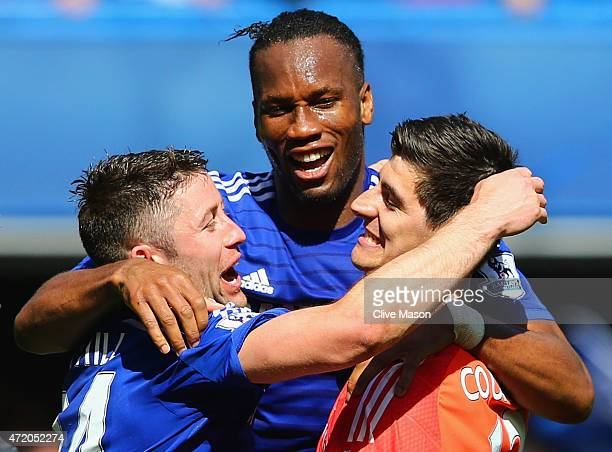 Gary Cahill Didier Drogba and Thibaut Courtois of Chelsea celebrate winning the Premier League title after the Barclays Premier League match between...