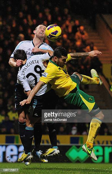 Gary Cahill of Chelsea battles with Bradley Johnson of Norwich City during the Barclays Premier League match between Norwich City and Chelsea at...