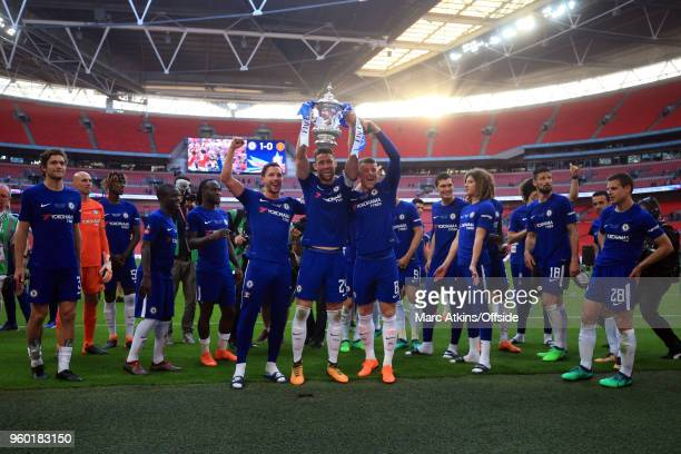 Gary Cahill of Chelsea celebrates with the trophy flanked by Ross Barkley and Danny Drinkwater during The Emirates FA Cup Final between Chelsea and...