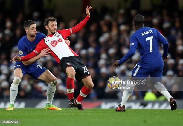 Gary Cahill of Chelsea holds up Manolo Gabbiadini of Southampton as he competes for the ball with N'Golo Kante of Chelsea during the Premier League...