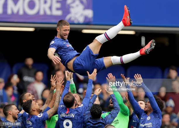 Gary Cahill of Chelsea is thrown up in the air by his team mates after the final whistle during the Premier League match between Chelsea FC and...