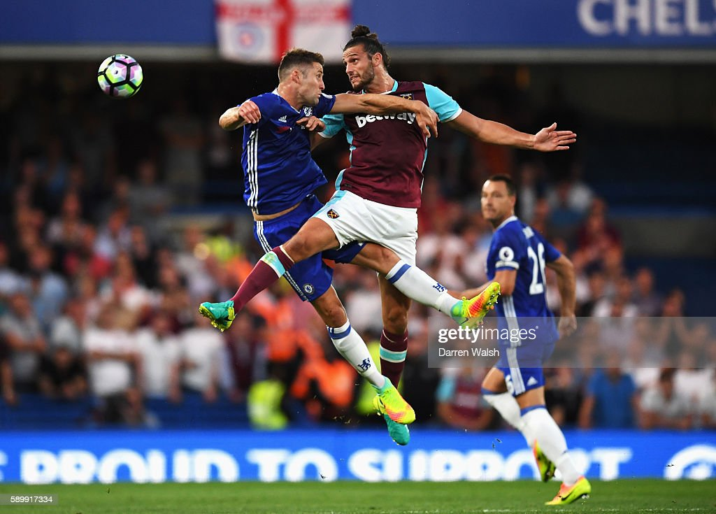 Gary Cahill of Chelsea jumps for a header with Andy Carroll of West Ham United during the Premier League match between Chelsea and West Ham United at Stamford Bridge on August 15, 2016 in London, England.