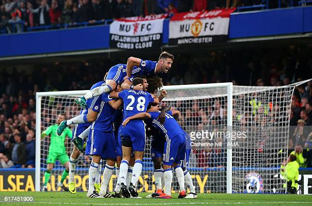 Gary Cahill of Chelsea jumps on tops as N'golo Kante of Chelsea celebrates with his team mates after he scores to make it 40 during the Premier...