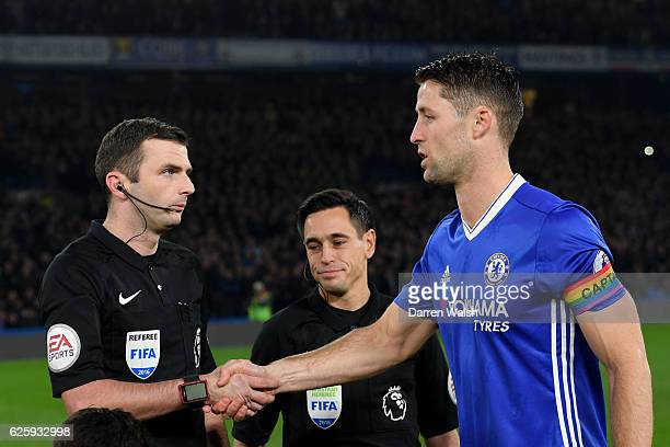 Gary Cahill of Chelsea wearing a rainbow colour captain's armband shakes hands with referee Michael Oliver prior to the Premier League match between...