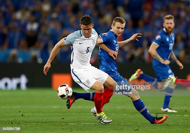 Gary Cahill of England and Jon Dadi Bodvarsson of Iceland compete for the ball during the UEFA EURO 2016 round of 16 match between England and...