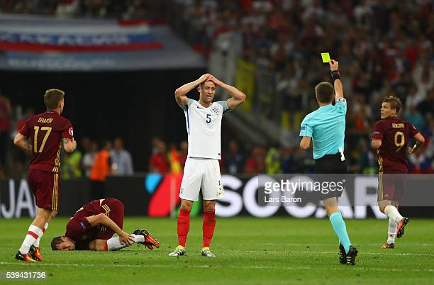 Gary Cahill of England is shown a yellow card by Referee Nicola Rizzoli during the UEFA EURO 2016 Group B match between England and Russia at Stade...