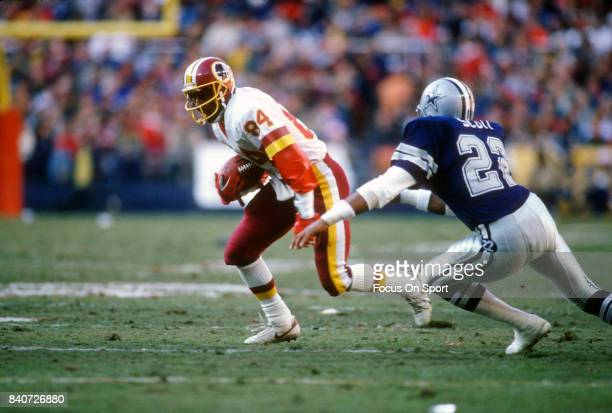 Gary Clark of the Washington Redskins running with the ball looks to put a move on Victor Scott of the Dallas Cowboys during an NFL football game...