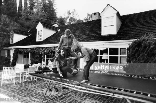 Gary Collins actor and wife Mary Ann Mobley former Miss America with daughter Clancy on the backyard trampoline December 9th 1980