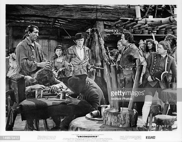 Gary Cooper aiming guns at group of men as Paulette Goddard watches in a scene from the film 'Unconquered' 1947