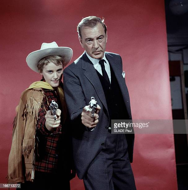 Gary Cooper And Maria Shell Poses In Studio Portrait studio de Gary COOPER en costume cravate aux côtés de Maria SHELL en chemise à carreaux avec un...