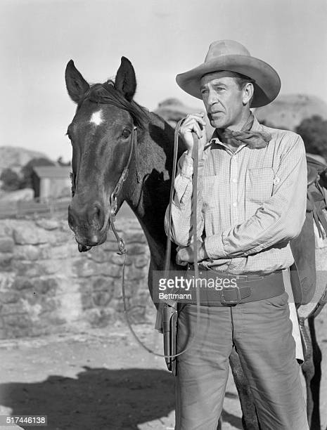 Gary Cooper stands alongside his horse in a scene from the 1945 comedic western Along Came Jones.